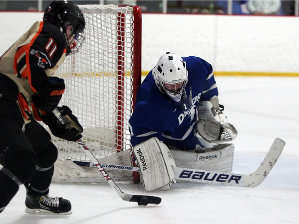 Danvers junior goalie Alex Taylor (1) makes a stick save on Beverly senior forward Ryan Santo (11). Taylor made 41 saves in regulation and overtime, however the Falcons fell 2-1 in a shootout in the D2 North Quarter Finals on Friday evening. DAVID LE/Staff Photo 2/28/14