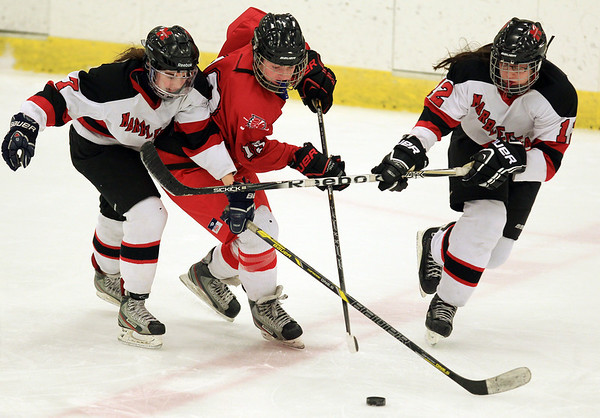 Masco sophomore Maddy Werner (19) tries to keep control of the puck while being stick checked by Marblehead forward Sydney Cresta (7) and defenseman Alanna Burke (12) during the first period of play on Thursday afternoon. DAVID LE/Staff Photo 2/6/14