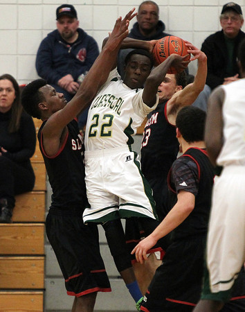 Lynn Classical junior Peter Mafo (22) gets his shot attempt blocked by Salem senior David Kazadi (5) and junior Bryan Martinez-Rodriguez (23) during the first half of play on Friday evening. DAVID LE/Staff Photo 2/14/14
