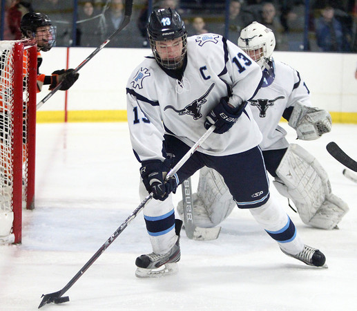 Peabody senior captain Giuseppe Zarro (13) manages to corral a loose puck in front of Peabody net minder Stephen Ferrante against Beverly in the 27th Annual Carlin Cup on Monday afternoon. DAVID LE/Staff Photo 2/17/14