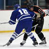 Danvers senior defenseman Ryan Cassidy (18) puts his shoulder into Beverly senior forward Graham Doherty (21). DAVID LE/Staff Photo 2/28/14