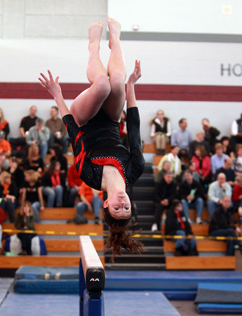 Masco gymnast Beth Defossez flips off the beam during the North Sectional Tournament held at Hudson High School on Saturday. DAVID LE/Staff Photo 2/21/14