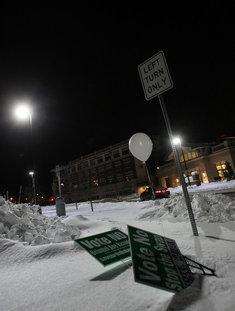 A couple signs opposing the proposed Brimbal Ave Project lie in the snow in the parking lot of Beverly High School where a vote was held on Saturday regarding the project. DAVID LE/Staff photo