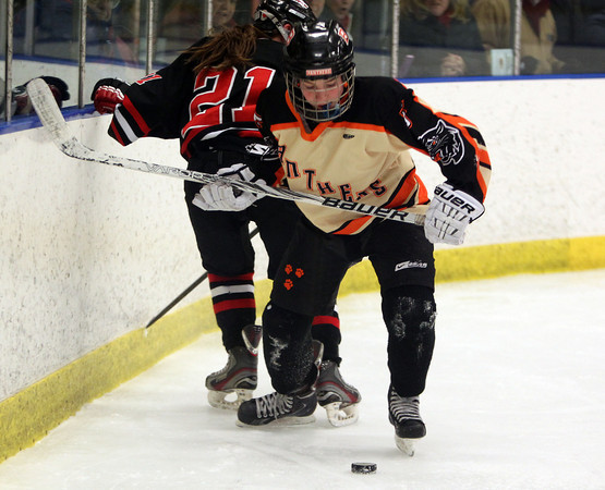 Beverly sophomore forward Kristen McCarthy (5) controls the puck behind the Hingham net after stealing it from Hingham sophomore defenseman Alissa Sullivan (21) during the second period of play on Saturday afternoon. DAVID LE/Staff Photo 3/1/14
