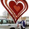 Ken Yuszkus/Staff photo: BEVERLY:  Roz Rideout of Beverly removes the wet snow from her car after purchasing chocolates at Winfrey's Fudge & Chocolates. The heart decoration was one of many in the window of the store. The snowstorm is expected to continue into Valentine's Day tomorrow.
