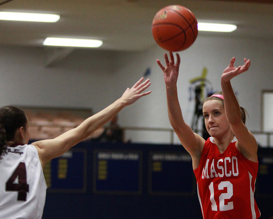 Masco senior captain Hannah Kiernan (12) drains a three over Lynn English senior Catherine Stinson (4) during the St. Mary's Spartan Classic on Monday evening at St. Mary's High School in Lynn. DAVID LE/Staff Photo 2/17/14