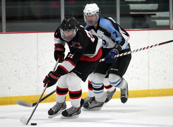 Salem freshman forward Mike Gillis (21) carries the puck up ice while being chased by Dracut sophomore Brian Smith (7) on Thursday evening. DAVID LE/Staff Photo 2/27/14