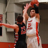Beverly senior captain Jon Berchoff (25) drains a three-pointer with North Andover senior Johnny Enright (23) right in his face on Tuesday evening. DAVID LE/Staff photo 2/25/14