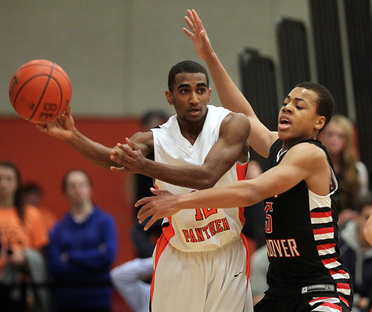 North Andover sophomore guard Wabissa Bede (5) plays tight defense on Beverly senior guard Jonangel Franco (12) on Tuesday evening. Bede and the Scarlet Knights defeated the Panthers 68-57 to advance in the D2 North State playoffs. DAVID LE/Staff photo 2/25/14