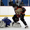 Beverly junior forward Jesse MacLaughlin (15) collides with Danvers junior goalie Alex Taylor (1) after he made a pad save during the first period of play on Friday evening. DAVID LE/Staff Photo 2/28/14