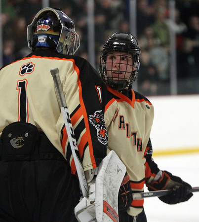 Beverly senior captain Connor Irving (22) has a word with Beverly junior goalie Tim Birarelli (1) before he took his penalty shot. DAVID LE/Staff Photo 2/28/14