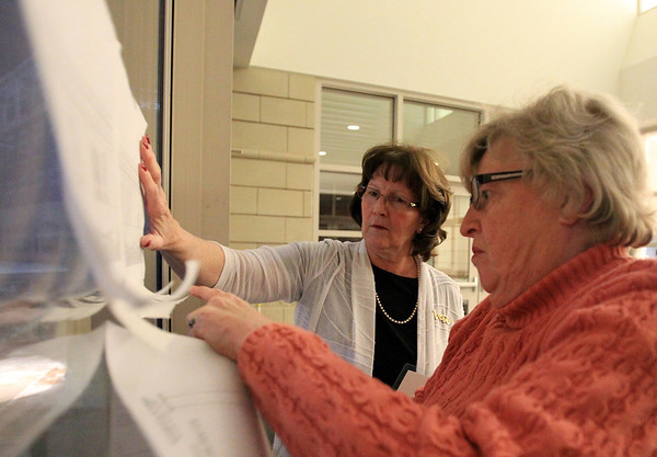 Beverly City Clerk Kathy Connolly, left, and Fran Macdonald, from the Beverly Board of Registrars, tape up the results from Saturday's vote regarding the proposed Brimbal Ave Project, on the doors of Beverly High School on Saturday evening. DAVID LE/Staff photo