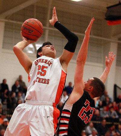 Beverly senior captain Jon Berchoff (25) sinks a short hook shot while being defended by North Andover senior Johnny Enright (23) on Tuesday evening. DAVID LE/Staff photo 2/25/14