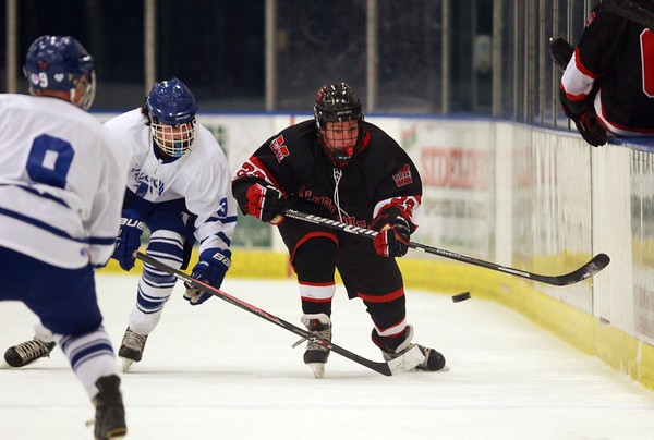 Marblehead senior Max DelVento (22) flips the puck up the boards past Danvers senior Trevor Daly (3) during the first period of play on Wednesday evening. DAVID LE/Staff Photo 2/12/14