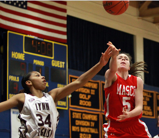 Masco junior guard Meghan Collins (5) gets fouled as she drives to the hoop by Lynn English senior Deirdra Newson (34) during the St. Mary's Spartan Classic on Monday evening at St. Mary's High School in Lynn. DAVID LE/Staff Photo 2/17/14