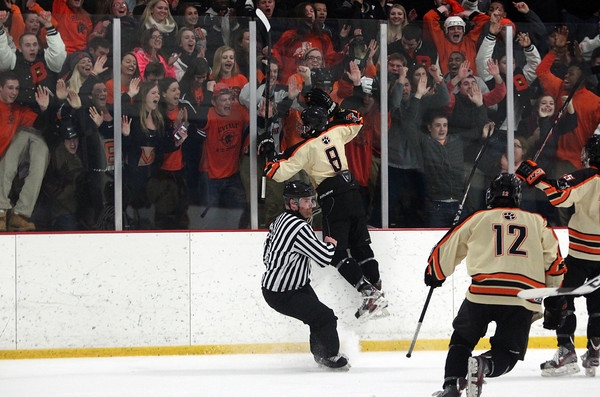 Beverly junior defenseman Nick Albano (8) leaps against the boards in celebration in front of the Beverly fan section after the Panthers defeated NEC Rival Danvers in the D2 North Quarterfinal on Friday evening. DAVID LE/Staff Photo 2/28/14