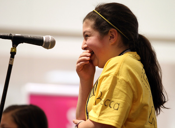 Higgins Middle Schooler Becca Dunn hides her giggle after principal Todd Bucey read the wrong sentence during the 4th Annual Peabody Higgins Middle School Spelling Bee on Wednesday evening. DAVID LE/Staff Photo 2/12/14