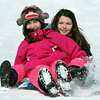 Sisters Courtney, 10, left, and Madeline Gray, 8, of Beverly, laugh while sledding down the hill at Lynch Park on Monday afternoon. DAVID LE/Staff photo