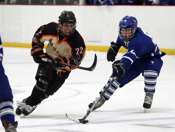 Beverly senior captain Connor Irving (22) tries to keep control of the puck while Danvers senior captain Kevin Hodgkins (8) tries to poke it away. Irving and the Panthers defeated the Falcons on penalty shots in the D2 North Quarter Finals on Friday evening. DAVID LE/Staff Photo 2/28/14