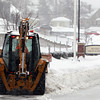A bulldozer clears snow at Beverly High School on Tuesday afternoon. DAVID LE/Staff Photo