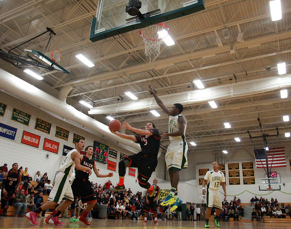Salem senior guard Jamie Dominguez (3) soars to the hoop as Lynn Classical senior Philip Rogers (11) goes up for the block during the first half of play on Friday evening. The Rams captured the NEC title with a 62-61 victory. DAVID LE/Staff Photo 2/14/14