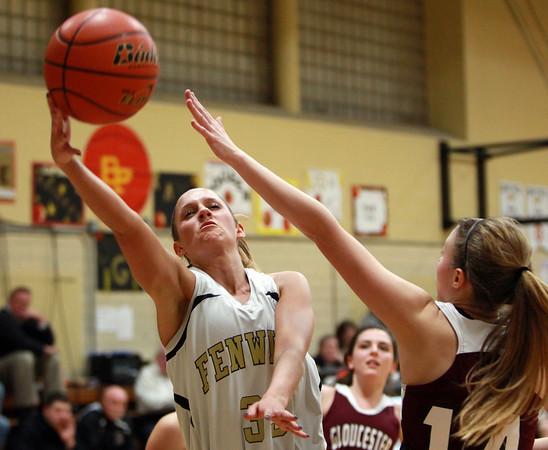 Bishop Fenwick senior captain Kate Lipka (33) flips a layup in off the glass over Gloucester's Hannah Ellis (14) during the first half of play on Thursday evening. DAVID LE/Staff photo