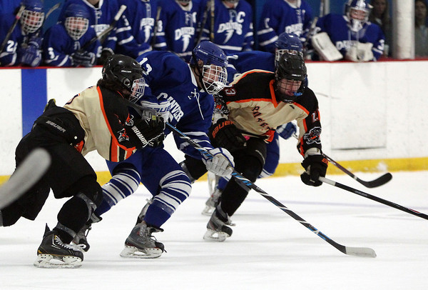 Danvers junior forward Kyle Cahill (13) gets sandwiched between Beverly senior forwards Kevin Lally (3) and JJ Bachini (23) while trying to keep control of the puck on Friday evening. DAVID LE/Staff Photo 2/28/14