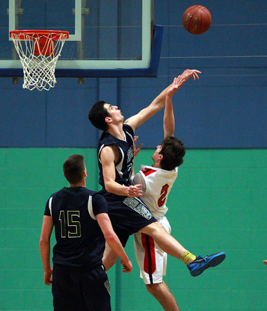 Pingree sophomore Justin Assad (24) records a huge block on PCD's Nick DeBlasio (2) during the second half of play. DAVID LE/Staff Photo 2/26/14