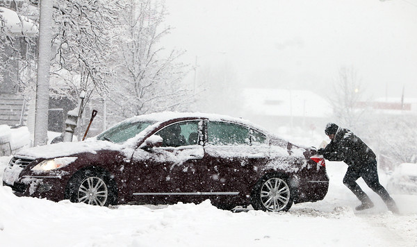 Beverly resident Marc Predka, right, tries to push his car into his driveway on Thursday afternoon in the midst of a heavy snowfall. DAVID LE/Staff photo