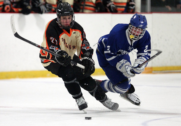 Beverly senior forward Graham Doherty (21) and Danvers junior forward Sean Lundergan (2) battle for a loose puck during the first period of play on Friday evening. DAVID LE/Staff Photo 2/28/14