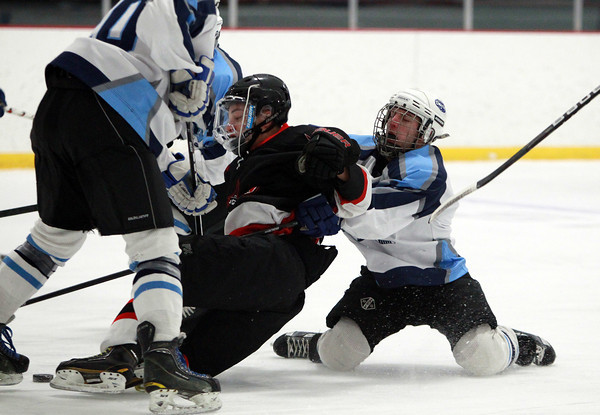 Salem senior forward Danny Heck (7) gets taken down by a Dracut player as he drives to the net during the first period of play on Thursday evening. DAVID LE/Staff Photo 2/27/14