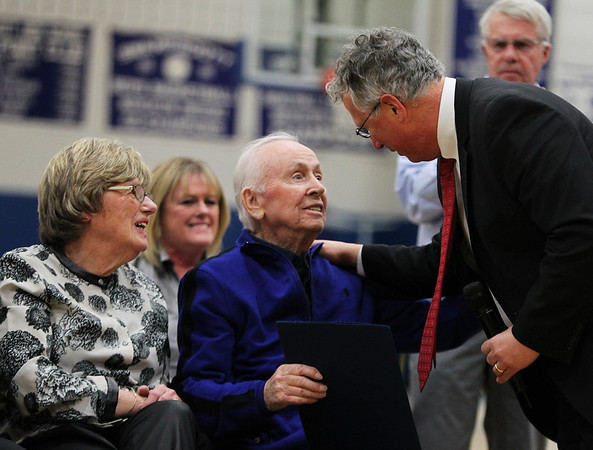 Senator Tom McGee, right, presents legendary Swampscott High School coach and athletic director Dick Lynch, center, with a plaque, as Joanne Lynch, left, looks on. DAVID LE/Staff photo