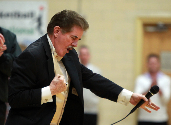 Rene Rancourt, local icon who sings the National Anthem for the Boston Bruins, gives his legendary fist pumps after performing the National Anthem at the start of the Bishop Fenwick and Gloucester girls basketball game at Bishop Fenwick High School on Thursday evening. DAVID LE/Staff photo