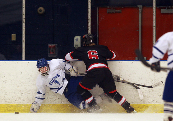 Marblehead sophomore defense PJ Roy (6) checks Danvers junior Erik D'Orlando (12) hard into the boards and separates him from the puck during the second period of play on Wednesday evening. DAVID LE/Staff Photo 2/12/14