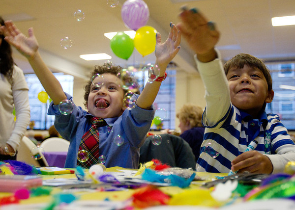 Four-year-olds Noah Este-McDonald, of Peabody, left, and Collin Furrier, of Melrose smile as they try and pop bubbles being blown while making Mardi Gras masks at St. Peter the Apostle Church's Mardi Gras Celebration on Tuesday evening. DAVID LE/Staff photo