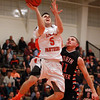Beverly senior guard Chris Sinclair (5) soars in for a layup while being closely defended by North Andover junior Brett Daley (11) on Tuesday evening. DAVID LE/Staff photo 2/25/14