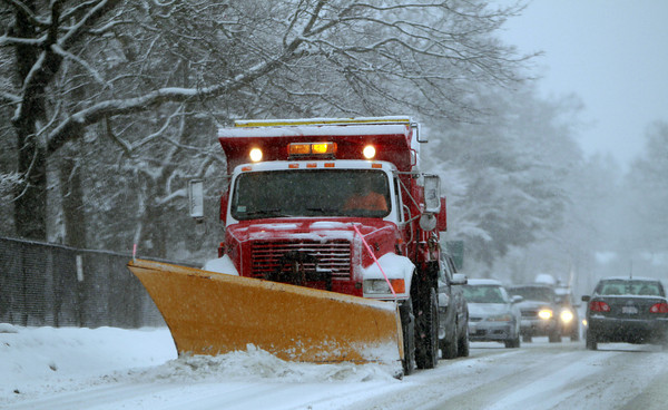 A plow slows up traffic along Liberty Hill Ave in Salem on Tuesday afternoon, starting the cleanup on another snowfall on the North Shore. DAVID LE/Staff Photo