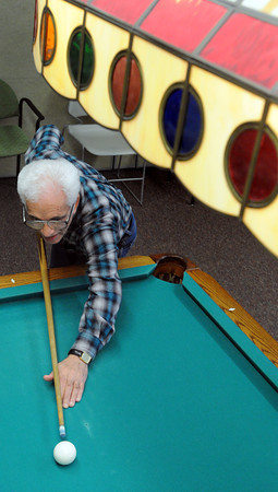 Ken Yuszkus/Staff photo: Beverly:  Sam Cokerden lines up a shot on the pool table while shooting pool at the Beverly Council On Aging Senior Community Center on Thursday.