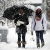 Monserrat College of Arts students Tiffany Binger, left, and Sentho Hunt, right, use an umbrella as they trudge along Dane St. through the heavy snow towards campus on Thursday afternoon. DAVID LE/Staff photo