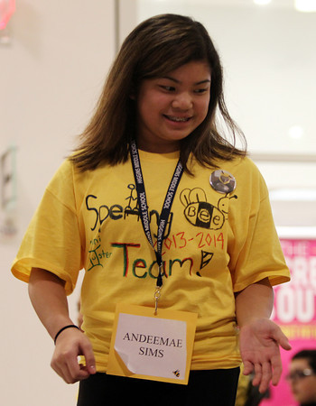 Higgins Middle Schooler Andeemae Sims gets a high five from one of her competitors during the 4th Annual Peabody Higgins Middle School Spelling Bee on Wednesday evening. DAVID LE/Staff Photo 2/12/14