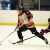Beverly sophomore forward Kristen McCarthy (5) controls the puck while being pursued closely by a Hingham player during the third period of play on Saturday afternoon. DAVID LE/Staff Photo 3/1/14