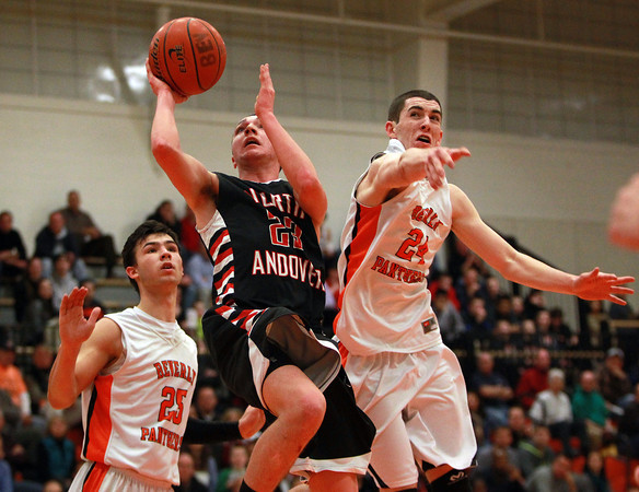 North Andover senior Johnny Enright (23) splits Beverly seniors Jon Berchoff (25) and Nick Cross (24) and glides in for an easy layup on Tuesday evening. DAVID LE/Staff photo 2/25/14