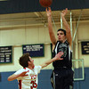 Pingree sophomore Justin Assad (24) shoots a three pointer with PCD's Ricky Pollock (35) right in his face on Wednesday evening. DAVID LE/Staff Photo 2/26/14