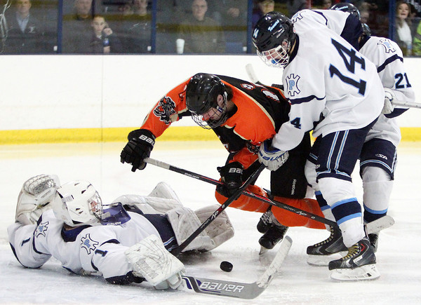Peabody junior goalie Stephen Ferrante (1) tries to find a loose puck while junior defenseman Cameron Smullen (14) tries to keep Beverly sophomore forward Ross Wahl (16) from finding the puck during the third period of play on Monday afternoon. DAVID LE/Staff Photo 2/17/14