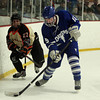Danvers junior defenseman Stephen Ganley (15) tries to clear the puck from behind his own net while being pursued closely by Beverly senior captain Connor Irving (22). DAVID LE/Staff Photo 2/28/14