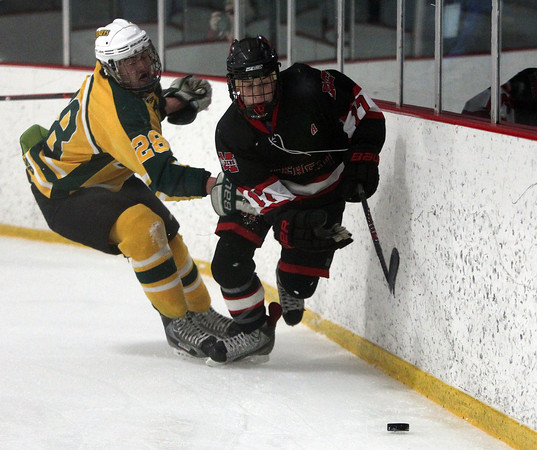 Marblehead senior captain Dean Fader (17) chases down the puck behind the North Reading net after beating Hornets senior captain Jake Laroche (28) in the D2 North Quarter Finals. DAVID LE/Staff Photo 2/28/14
