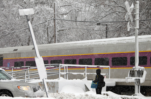A commuter rail passenger waits patiently for the train to pass by after getting dropped off in the middle of a heavy snowfall at the Monserrat Train Station on Thursday afternoon. DAVID LE/Staff photo