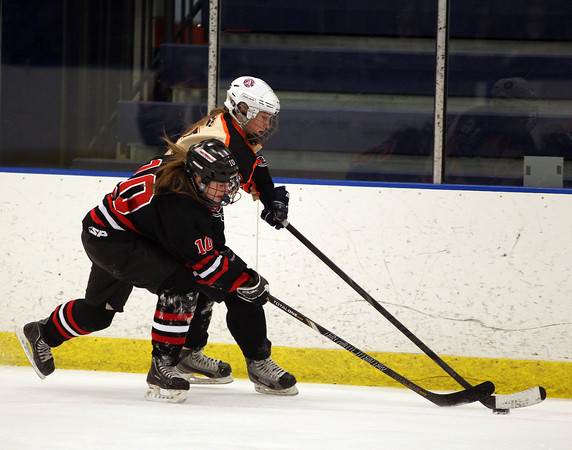 Beverly forward Julia Nearis (16) uses her body to shield Hingham defenseman Rachel d'Entremont (10) from the puck while carrying it along the boards in the Panthers offensive zone. Nearis scored a goal with 37.1 seconds remaining in the third period to lift the Panthers over the Harbormen 3-2 at the Rockett Arena at Salem State University on Saturday afternoon.DAVID LE/Staff Photo 3/1/14