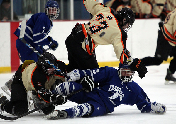 Danvers junior forward Kyle Cahill (13) gets taken down by Beverly senior forward Kevin Lally (3) and senior forward JJ Bachini (23) after being separated from the puck on Friday evening in the D2 North Quarter Finals at Stoneham Arena in Stoneham. DAVID LE/Staff Photo 2/28/14