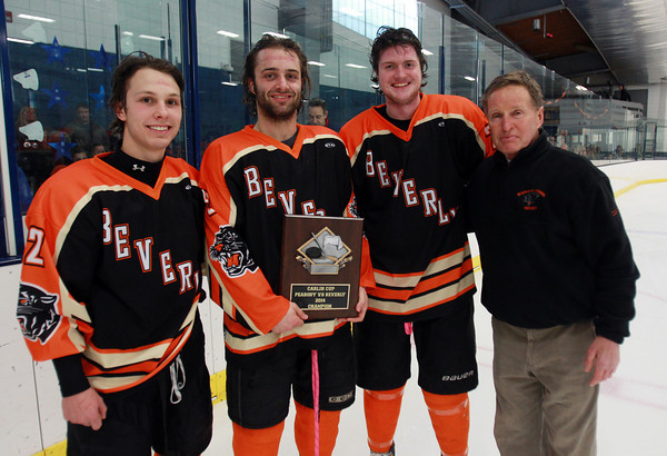 From left, Beverly senior captains Connor Irving, Matt Hamor, Sean Munzing, and Head Coach Bob Gilligan with the Carlin Cup trophy after downing Peabody 8-1 in the 27th Annual Carlin Cup at the McVann O'Keefe Rink in Peabody on Monday afternoon. DAVID LE/Staff Photo 2/17/14